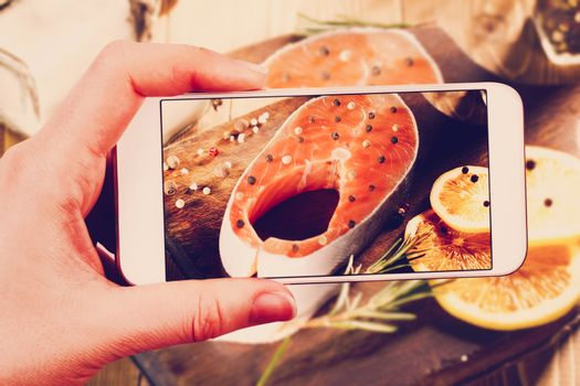 Using smartphones to take photos of raw salmon steak with instag