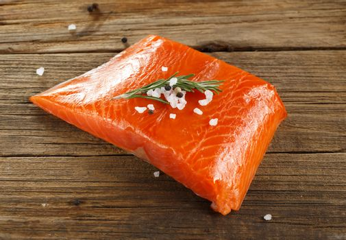 Salmon steak with herbs on wooden background.