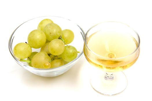 Glass of wine and grapes on bowl on white background