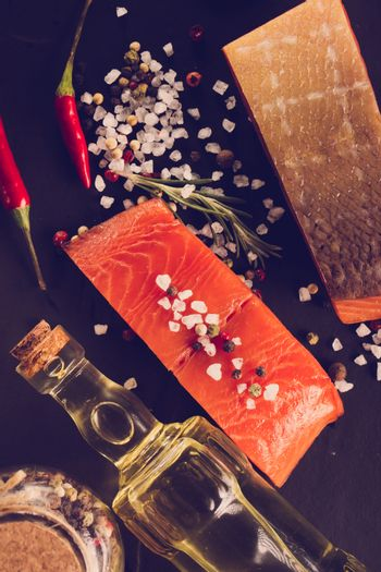 Salmon steak with herbs on black background. In the style of ins