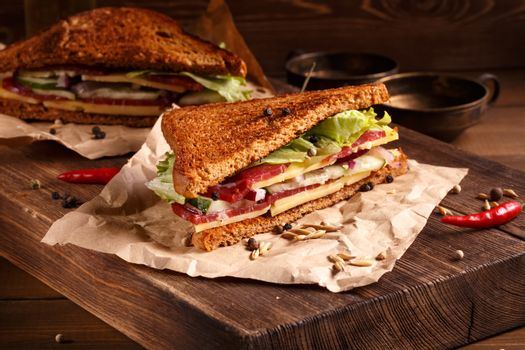 Two pieces of club sandwich on old papper with big cutting board