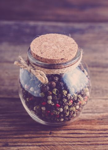 Vintage jar with spices on a wooden background.