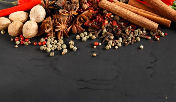 Herbs and spices on black background with space for text.