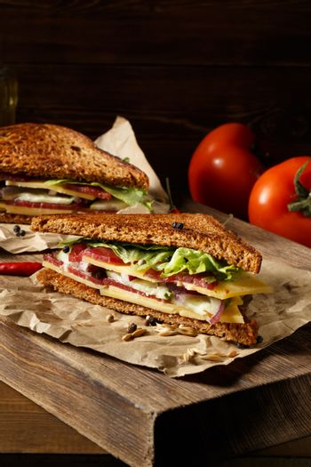 Two pieces of club sandwich on old paper with big cutting board