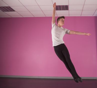 Focused male ballet dancer leaping up