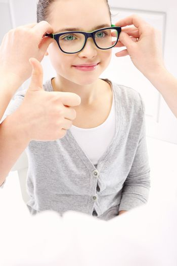 Selection of glasses, a little girl with an ophthalmologist.