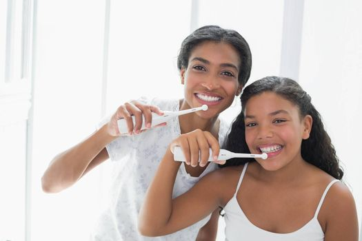 Pretty mother brushing her teeth with her daughter at home in bathroom