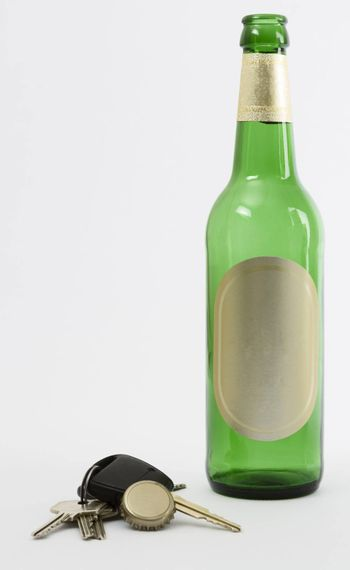 empty beer bottle with car key and crown cork isolated in grey background.