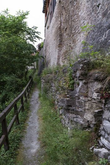 small path with wooden handrail and historic wall