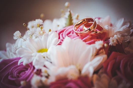 two wedding rings on top of bouquet
