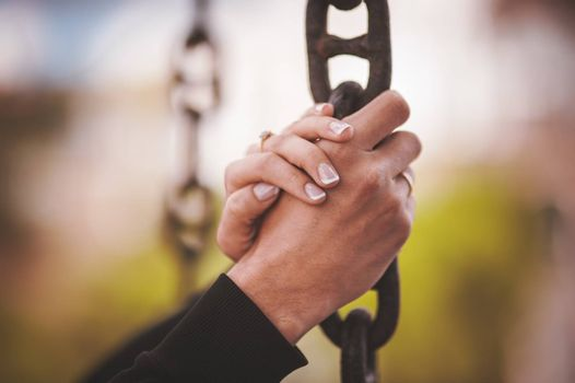 couple holding hand together on metal chain