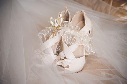 white brides wedding shoes and white garter