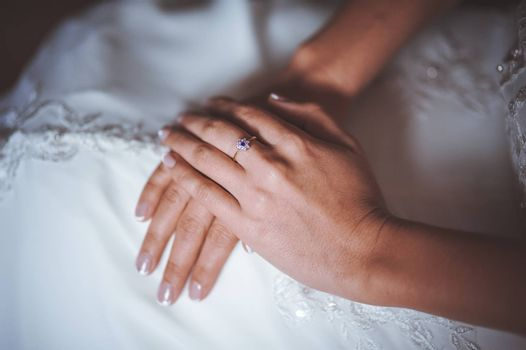 hands of bride with ring crossed on legs