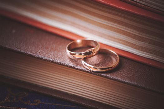 two wedding rings on top of books