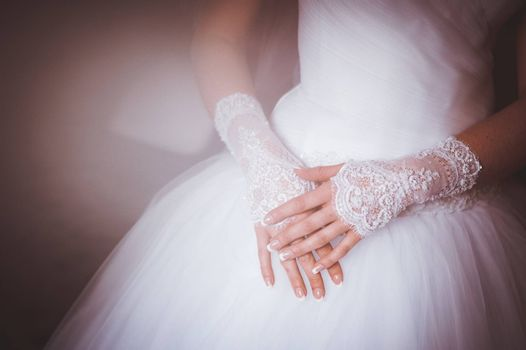 hands of bride in gloves crossed on legs