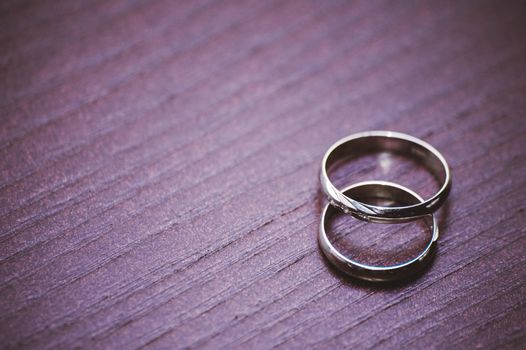 two wedding rings laying on wooden table