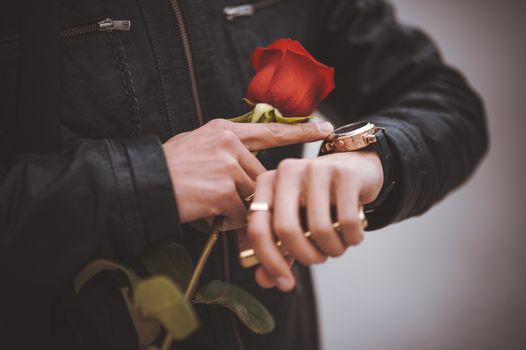 men waiting for his date and chacking time with red rose in hands
