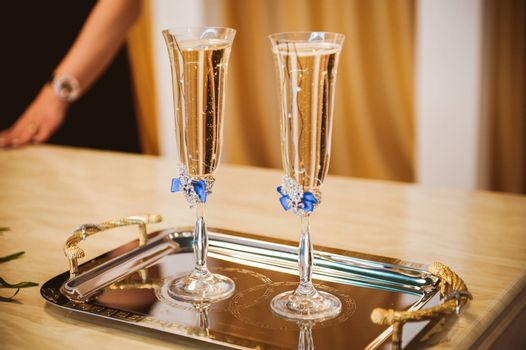 two champagne glasses decorated with blue bow