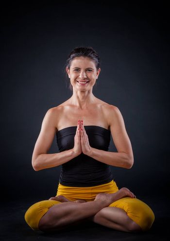 Pretty brunette woman doing yoga. Shot on black background