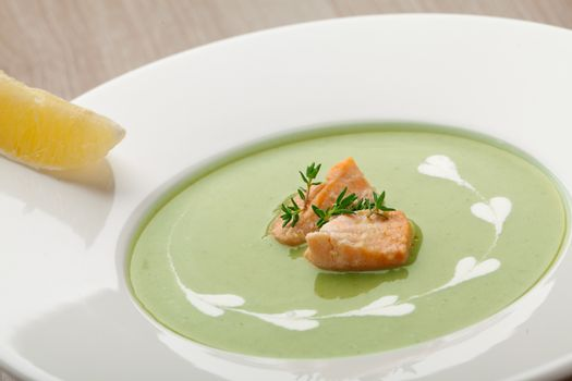 Green cabbage broccoli cream soup puree in white plate  served with  filleted salmon pieces , lemon and  theme