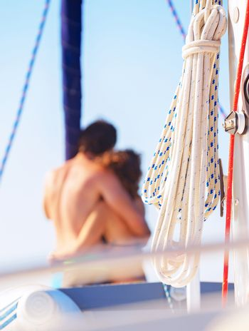 Selective focus on a  happy loving couple standing on the mast of yacht and hugging, romantic relationship, summer vacation, love concept