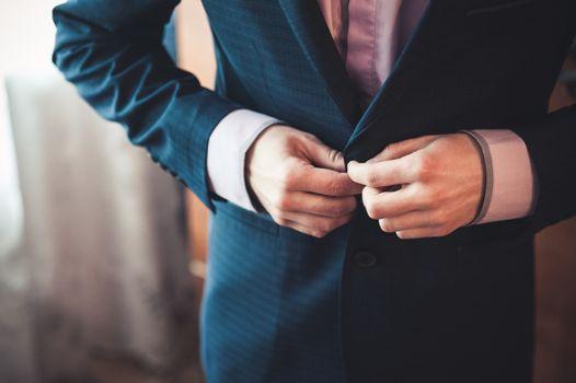 men fastens his black suit no face