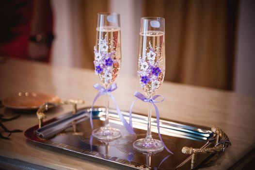 decorated with purple flowers and bow champagne glass