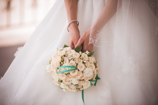 bride holding wedding bouquet from white roses with green ribbon