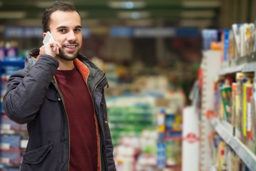 Smiling Young Man Using Mobile Phone While Shopping In Shopping Store