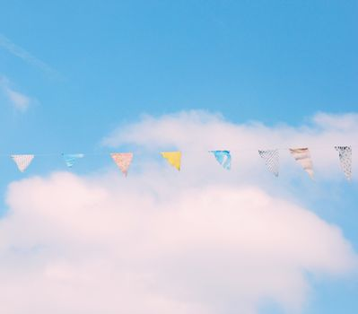 Colorful bunting flags on blue sky with retro filter effect