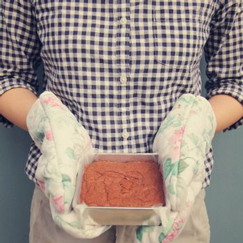 Woman holding brownie taken out of oven, retro filter effect