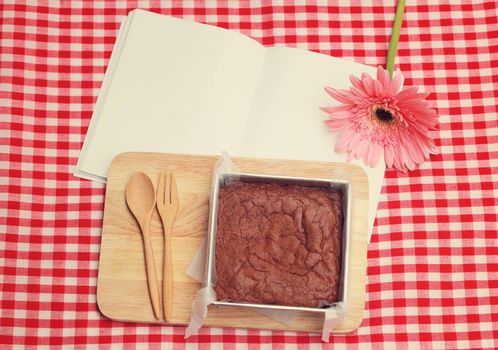 Homemade brownie on blank notebook with retro filter effect
