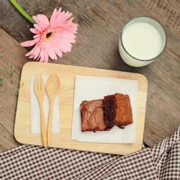 Tasty brownies with glass of milk and flower, retro filter effect