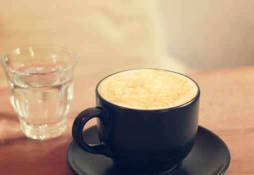 Hot cup of caramel macchiato with glass of water, retro filter effect