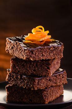 Homemade Chocolate Brownie on a dark plate against a dark background