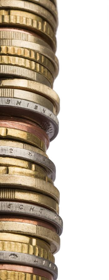 huge tower of different euro coins in close up shot isolated in white background