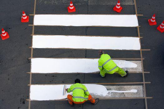 workers painting crosswalk