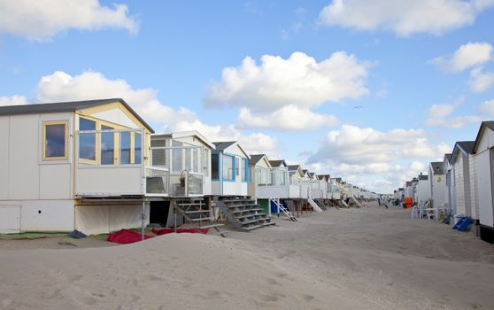 Beach houses on beach in a row with blue sky