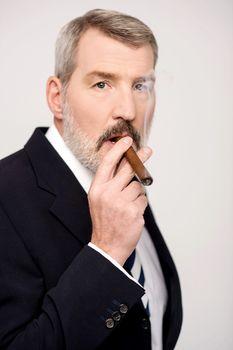 Aged man smoking cigar over white