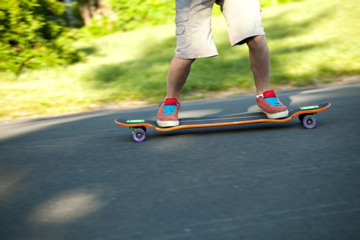 Action shot of a longboarder skating on a suburban road. Shallow depth of field.