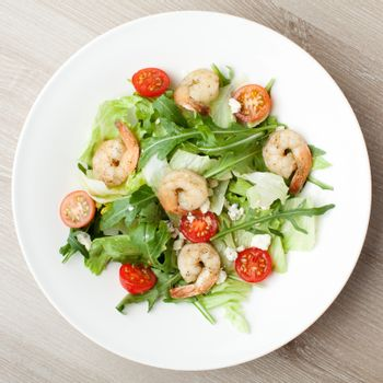 Fresh gourmet seafood salad with lettuce, rocket and corn greens, shrimps, cherry tomatoes, cheese  served in white plate