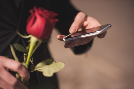 men holds red rose while calling on mobile phone