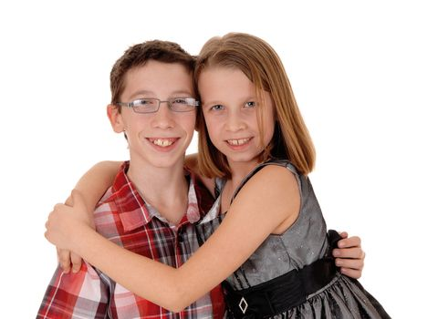 A little sister is hugging her older brother, isolated on white background.