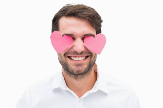 Handsome man with hearts over his eyes on white background