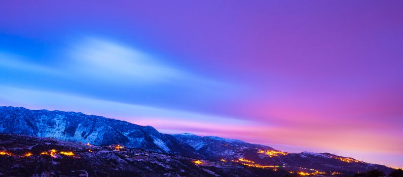 Beautiful mountains panoramic winter landscape, gorgeous natural border, majestic colorful sunset sky over high mountains covered with snow