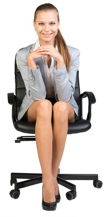Businesswoman on office chair, with hands clasped under her chin