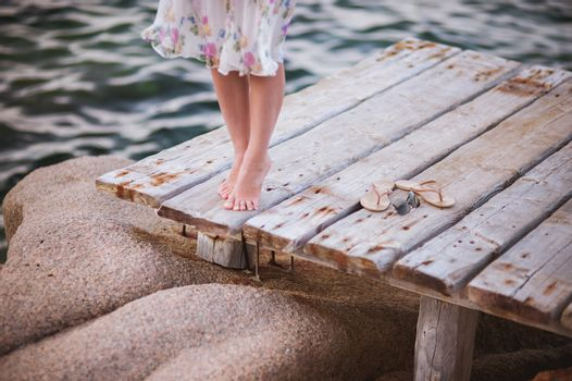barefoot girl on wooden bridge above water no face