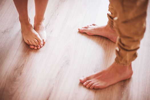 barefoot couple standing on wooden floor no face