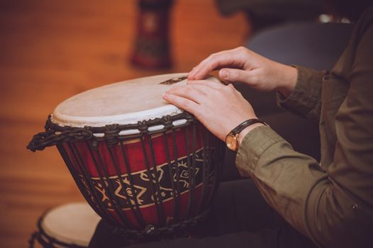 person playing on Jambe Drum no face
