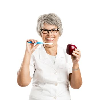 Senior nurse holding a apple and a toothbrush